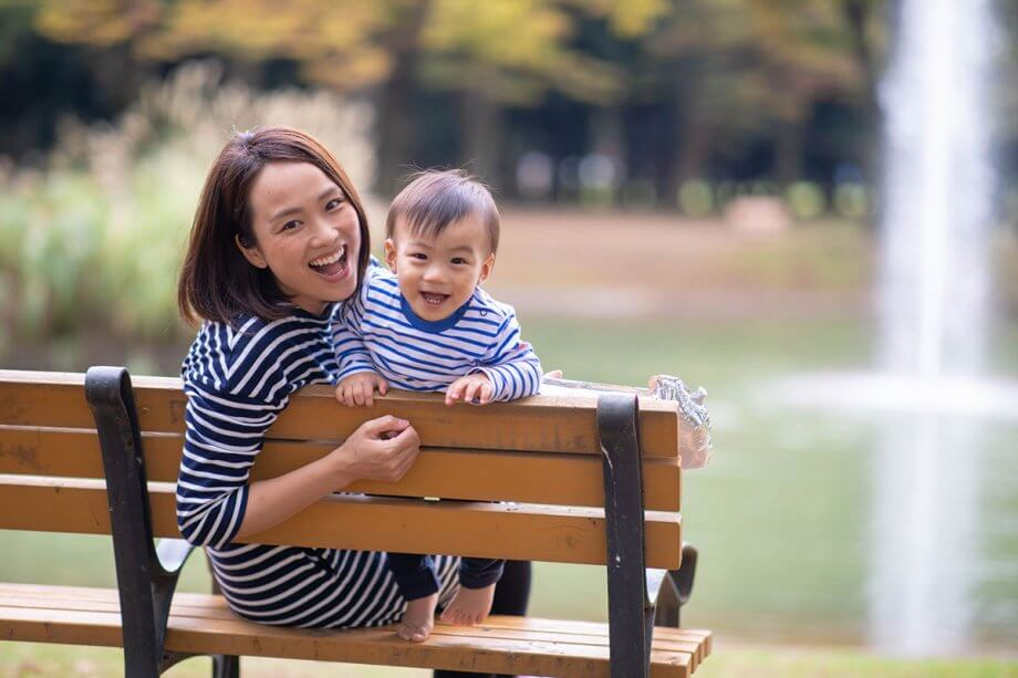Mom and toddler, both wearing navy and white striped shirts, sitting on park bench, smiling