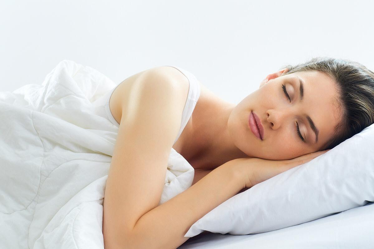 woman in bed, sleeping on side