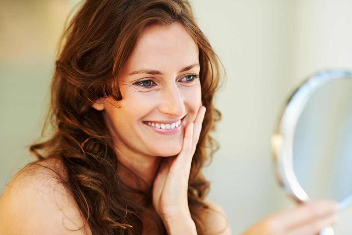 woman with long brown hair looking to a hand mirror and smiling at herself