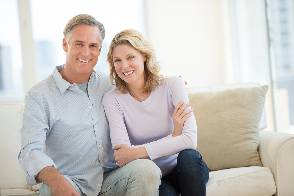 middle-aged couple sitting on beige couch, smiling