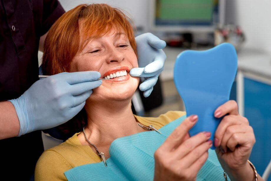 woman in dental chair looking in mirror as dentist points to her teeth